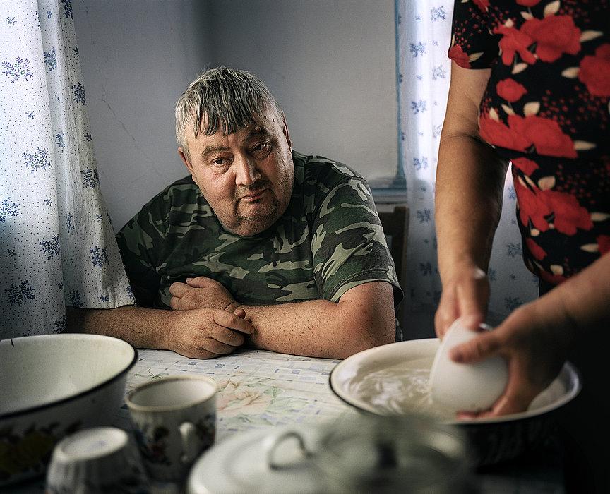 Dolon, Kasachstan, 2010. Der geistig behinderte Alexander, geboren 1958, ist in allem auf fremde Hilfe angewiesen. Seine Mutter, Ludmila Schakworostowa hat zwei Söhne, die beide durch die Auswirkungen der Atombomentests schwer krank sind. In ihrer geistigen Entwicklung sind sie auf der Stufe eines Kleinkinds stehen geblieben.
